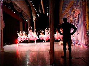 Jay Goodlett, at right, waits offstage as dancers perform. 