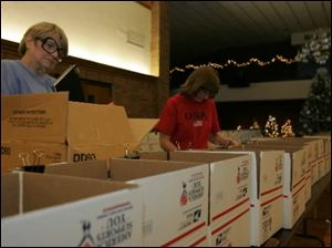 Sharron Pinkley, left, and Cheryl Thompson help get 400 boxes ready for shipment.
