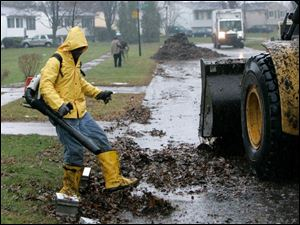 Norman Sharpley uses a leaf blower as part of a crew collecting leaves on Bloomfield Avenue.