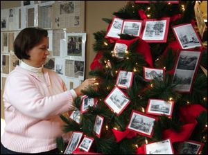 Jennifer Wenzel puts final touches on a Christmas tree in the Summerfield Petersburg Branch Library.