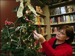 Doris Sheldon adds to the holiday atmosphere in the Summerfield Petersburg Branch Library.