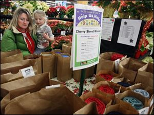 At left, Dawn Miller and her daughter Claire, 6, pick out a  Help Us Help  bag to purchase at The Andersons store on Talmadge Road.