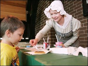 Janet Rasmussen adds sprinkles to a Christmas cookie for Jacob Sullivan of Oregon at the Fort Meigs Holiday Open House Sunday.