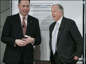 Mike Thaman, chairman and CEO of Owens Corning, left, stands with T. Boone Pickens after signing Mr. Pickens' energy plan during a visit Monday to Owens Corning Headquarters.