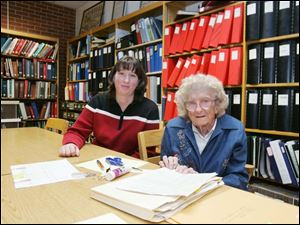 Jennifer Fording, left, and Grace Luebke, who collected much of the archives in the library, discuss putting the precious records on line to preserve them for many generations to come.
