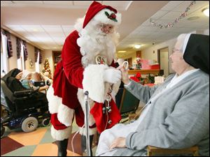 Sister Jean Francis Boes, right, gets a treat from Santa, aka Tim Stapleton, during his annual visit to the sisters  convent.