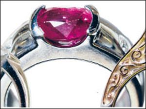 Left: Engagment ring with yellow center stone. Center: White gold fashion ring has an oval ruby and diamonds. Right: White gold ring has scrollwork on both sides.