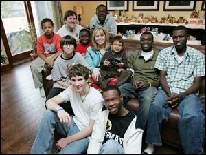 The Frisch family. In the front row are Conner, left, and Joadson. In the center are Cole, left, Charlie (in the red shirt), Jackie, Isaiah, Moise, and Fabenson. In the back row are Mekail, left, Aaron, and Max. Not pictured are Blade and Megail.