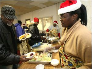 Disha Brooks serves salad to Mike Mickles at Thomas Temple Church of God in Christ. This is the fourth year for the church's holiday meal.