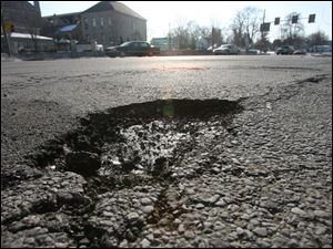 One of the city's large potholes is located on the corner of West Bancroft Street and North Detroit Avenue.