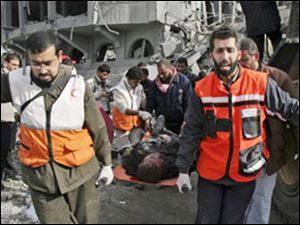 Palestinian medics carry the body of a security force officer from Hamas after an Israeli missile strike at the former headquarters of Palestinian President Mahmoud Abbas in Gaza City on Saturday.