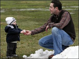 Jeff Kryspin of Whitehouse and his son Ian, 18 months, play in the snow. Or play in what's left of it. True, they could have made snowballs last week, when the ground was white, not green, brown, and waterlogged. But, Mr. Kryspin said, it was just too doggone cold back then.