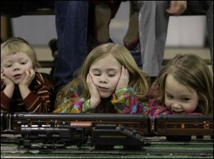 Jack Dieter, 2, left, and his sisters, Sophia, 6, and Irene, 5, keep a close eye on the passing O-gauge trains owned by Bill Frankman of Greenville, Ohio. The three Maumee children were with their parents, Aaron and Kristy Dieter, yesterday.