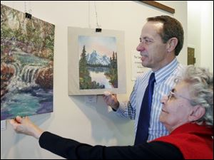 Fred Moor and Martha Baldoni examine the artwork on display this month in the Perrysburg Municipal Court Building.