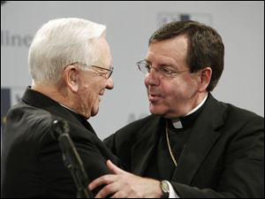 Associated Press Cardinal Adam Maida, left, congratulates his successor, Bishop Allen H. Vigneron, who was named archbishop of the Detroit diocese. The appointment was announced yesterday.