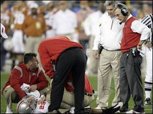 Ohio State coach Jim Tressel, right, and Texas coach Mack Brown watch medical personnel work on Shaun Lane.