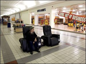 Tom Lucet of Beverly, Mass., takes a solitary break in the Liberty Tree Mall in Danvers, Mass., where clothing retailer Steve & Barry's, a victim of the sour economy, holds a going-out-of-business sale.