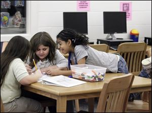 Nancy Potts, 10, left, and sister Shelby Potts, 11, get some help from Myah Reed, 11, during the PowerHour after-school homework program through the Boys and Girls Club of Toledo at Sherman Elementary.