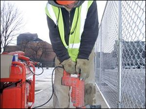 Scott Easterwood, an employee of Rudolph-Libbe, drills brackets for a fence at Superior and Jackson streets in downtown Toledo, site of the United Way s new headquarters. The six-foot-high chain-link fence put up yesterday was the first visible sign that a new United Way headquarters will be erected in the shadow of the old building. The Toledo Plan Commission in November gave its OK for work on the building to proceed.