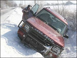 Joe Crapsey helps Fatima Hashmi after her Land Rover slipped into a ditch on Roachton Road in Perrysburg on Thursday.