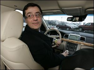 In a 2010 Lincoln MKS, Ali Jammaol, an engineer with Ford Motor Co., demonstrates the vehicle's self-parking function he helped design. Its steering system uses an electric motor rather than hydraulics.