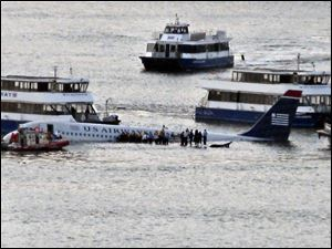 Passengers wait on the wings of a US Airways Airbus to board boats after the jetliner safely landed on the Hudson River.