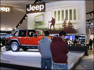 Michael Lotz, left, and Seth Myers inspect the Jeep Rubicon at the Detroit auto show, which opened to the public yesterday.