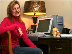 Michele Howe works in the office of her Michigan home. At right are some of her books.