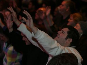 Marty Self of Holland lifts his hands in prayer during the opening of the Holy Toledo Day of Prayer at the Valentine Theatre.