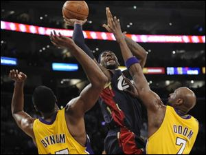 Cavaliers forward LeBron James shoots over Lakers center Andrew Bynum, left, and forward Lamar Odom in first half Monday night.