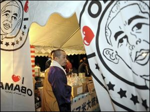 Chief priest Shoryu Tamagawa with the Haga-ji temple visits a tent decorated with portraits of President Obama as this northern Japan city of Obama celebrates the inauguration Tuesday.