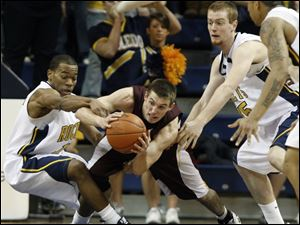 With Ian Salter applying pressure, Toledo guard Larry Bastfield, left, reaches for the ball but winds up grabbing the arm of Central Michigan s Robbie Harmon last night at Savage Arena.