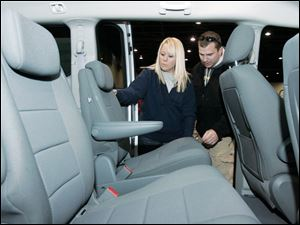 Amy and Brett Bethel examine a Dodge Grand Caravan SE at the Toledo Auto Show. The Bethels, who have two young children, are looking into the prospect of getting a larger vehicle soon.