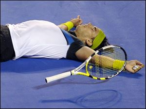 After playing five sets that lasted 4 hours, 22 minutes, Rafael Nadal celebrates his exhausting Australian Open victory. Roger Federer was emotional after failing to match Pete Sampras' Grand