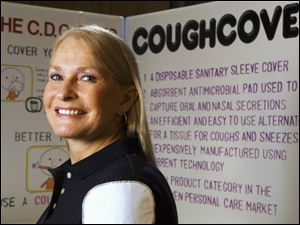 Retired nurse anesthetist Michele Strocel models the CoughCover on her shoulder. CoughCover is a pad that sniffly people can affix to their shirts and cough or sneeze into.