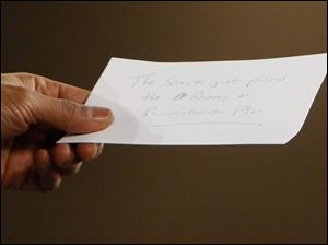 President Obama holds a note with the w