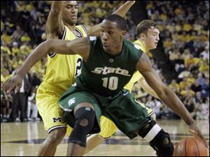 Michigan State forward Delvin Roe (10) is defended by Michigan guard C.J. Lee during the first half last night at UM's Crisler Arena. Roe scored 11 of his season-high 14 points in the half, while teammate Kalin Lucas had 13 of his 15 points after halftime.