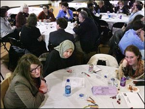 Michelle Niedermier, left, of Lucas County Job and Family Services, Sanaa Eid, and Rachel Davies discuss poverty at a forum conducted by the Ohio Association of Community Action Agencies. The group will gather information to send to Gov. Ted Strickland.