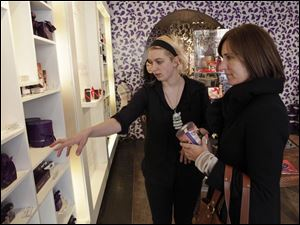 Salesman Sonja Drummond, left, helps customer Nicki Brashear at the Vosges Haut Chocolat store in Chicago. Analysts and experts predict Americans will spend less this year on Valentine's Day gifts such as chocolate and dinners.