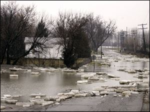 Water and ice from the River Raisin cover Winchester Street in Monroe. The river spilled its banks at Veterans Park as well.
