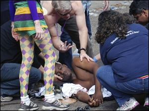 An unidentified shooting victim is aided after gunfire broke out following the last major parade of New Orleans' Mardi Gras. Seven people were injured and two men were taken into custody.