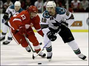 Sharks defenseman Dan Boyle moves the puck as the Wings' Pavel Datsyuk tries for the steal in the first period last night.