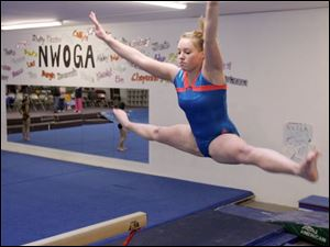 Napoleon junior Kendall Homan practices on the balance beam. Homan is a two-time defending all-around champion at the district and finished 15th at state last year.