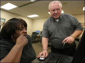 John Lula, right,  instructor of a basic computer class at The Source, works with Theressa Morgan.