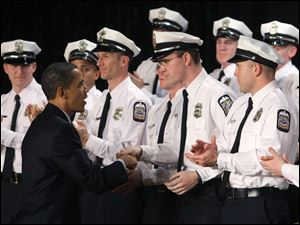 President Obama congratulates police recruits during their graduation ceremony in Columbus. The new officers faced layoffs until funds from the economic stimulus plan arrived.
