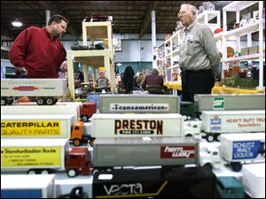 Vendor Don Scheuring of Parma Heights, Ohio, right, stands ready to answer questions from John Quinn of Cleveland at the 95th Toledo Collectors' Toy Fair at the Lucas County Recreation Center.