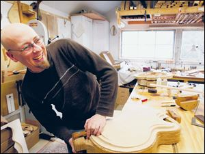 Denny Kopp clamps a guitar top before carving it in his shop.