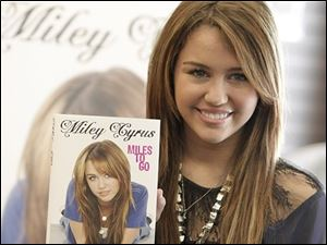 "inger and actress Miley Cyrus poses with a copy of her book ""Miles To Go"" at a book signing at Barnes & Noble in Los Angeles on Saturday, March 7, 2009."