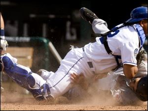 The Indians' Grady Sizemore is tagged out by Royals catcher Miguel Olivo while trying to score from third on a wild pitch in the ninth inning.