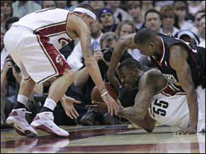 Cavaliers Lorenzen Wright (55) and Delonte West, left, fight for the basketball.